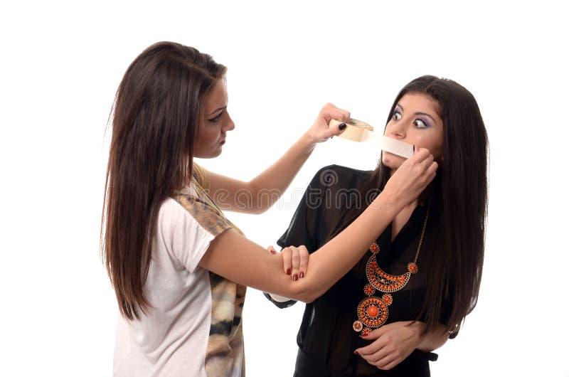 Muchacha que pone a la cinta aislante sobre su boca de los amigos imágenes de archivo libres de regalías
