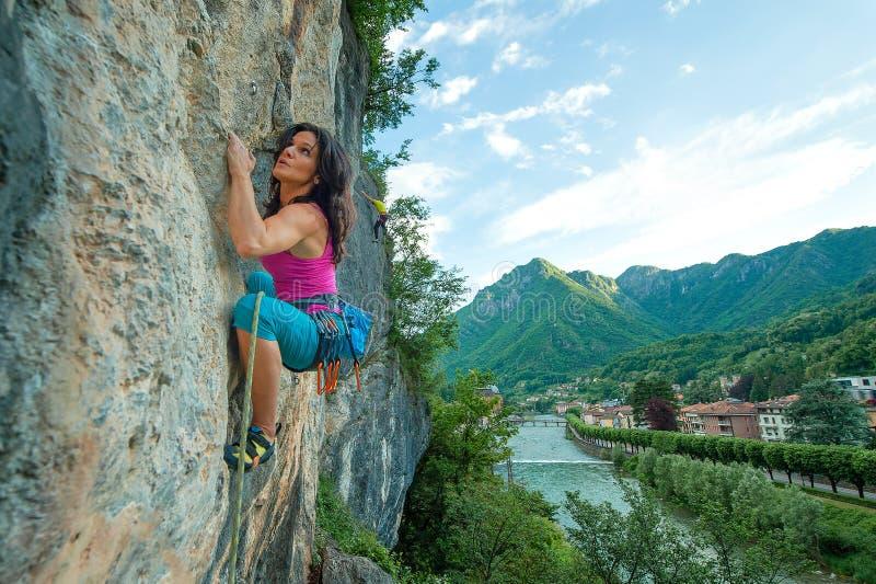 Muchacha que practica libremente el subir en roca con el panorama del chalet imagenes de archivo