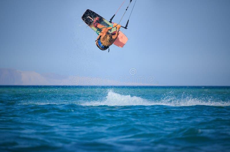 Muchacha que practica surf de la cometa en traje de ba?o atractivo con la cometa en cielo a bordo en ondas que montan del mar azu imagen de archivo