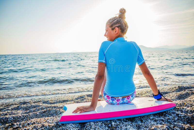 Muchacha que practica surf feliz foto de archivo libre de regalías