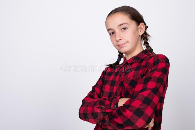 Muchacha que presenta con brazos cruzados y un peinado muy bonito imagen de archivo libre de regalías