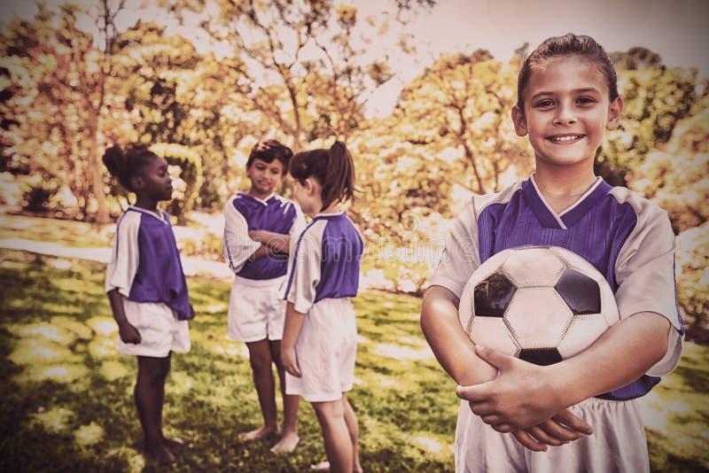Muchacha que presenta con su equipo de fútbol en el fondo imagen de archivo