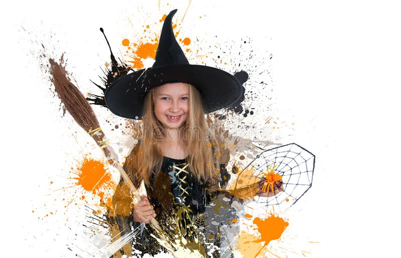 Muchacha que presenta en vestido de la bruja con la escoba y la araña, pequeña bruja de Halloween imagen de archivo