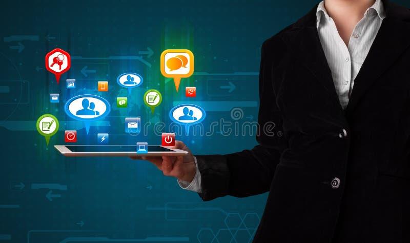 Muchacha que presenta una tableta con los iconos y las muestras sociales coloridos fotos de archivo libres de regalías