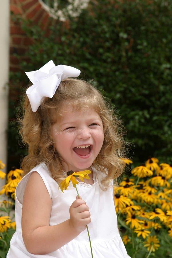 Muchacha que ríe y que sostiene la flor fotografía de archivo