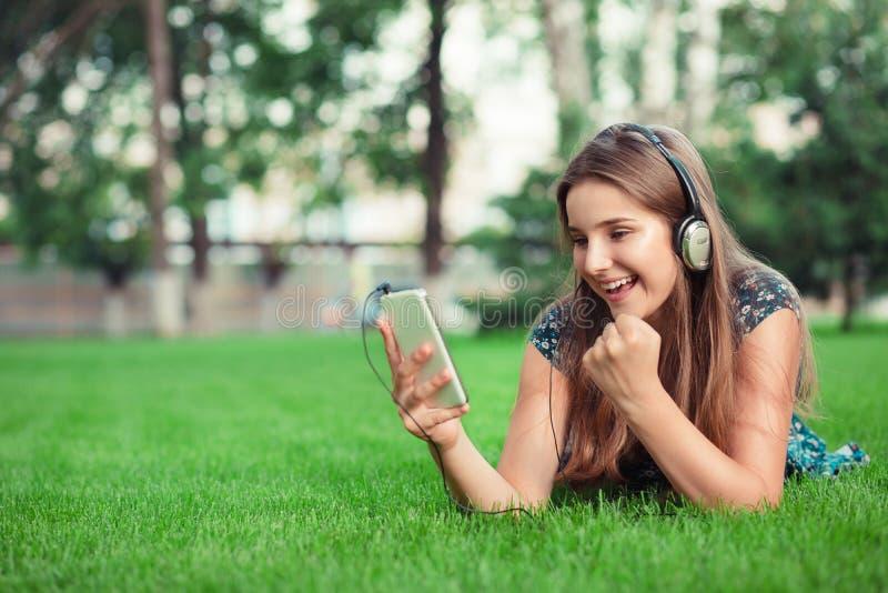 Muchacha que recibe un mensaje del SMS con buenas noticias en un teléfono móvil foto de archivo libre de regalías