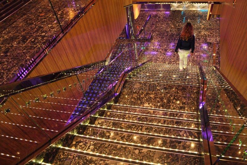 Muchacha que recorre abajo de pasos de progresión de escaleras brillantes grandes fotografía de archivo