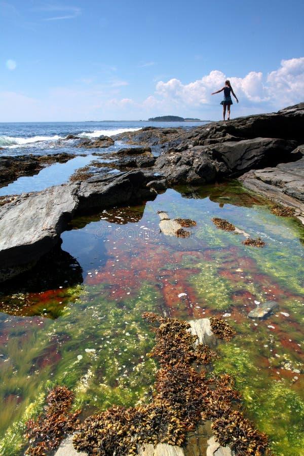Muchacha que recorre en la playa rocosa imagenes de archivo