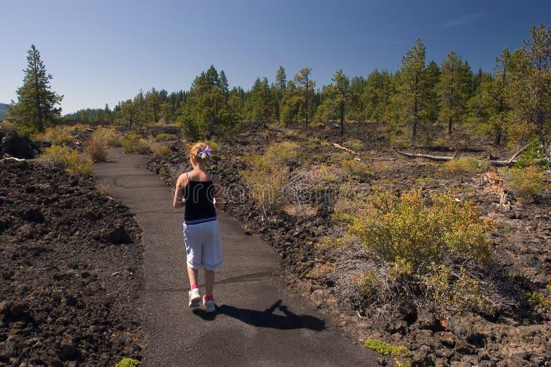 Muchacha que recorre a través de rocas de la lava fotos de archivo