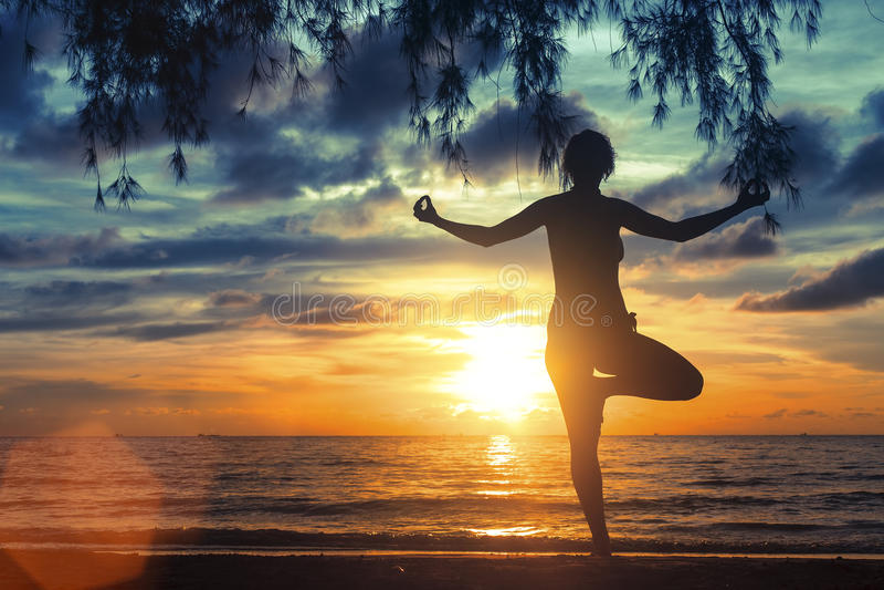 Muchacha que reflexiona sobre la playa del mar durante una puesta del sol maravillosa Yoga y aptitud imagenes de archivo