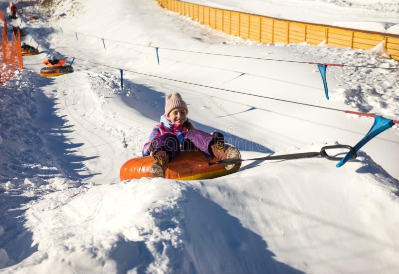 Muchacha que resbala para arriba en los tubos de la nieve imagenes de archivo