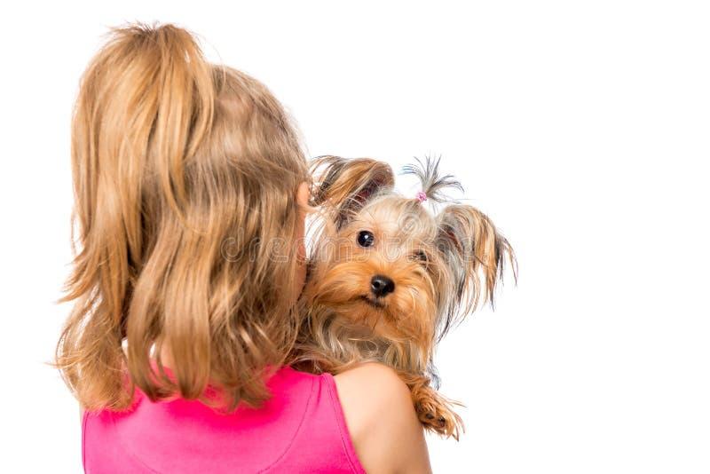 Muchacha que retrocede y que sostiene Terrier foto de archivo