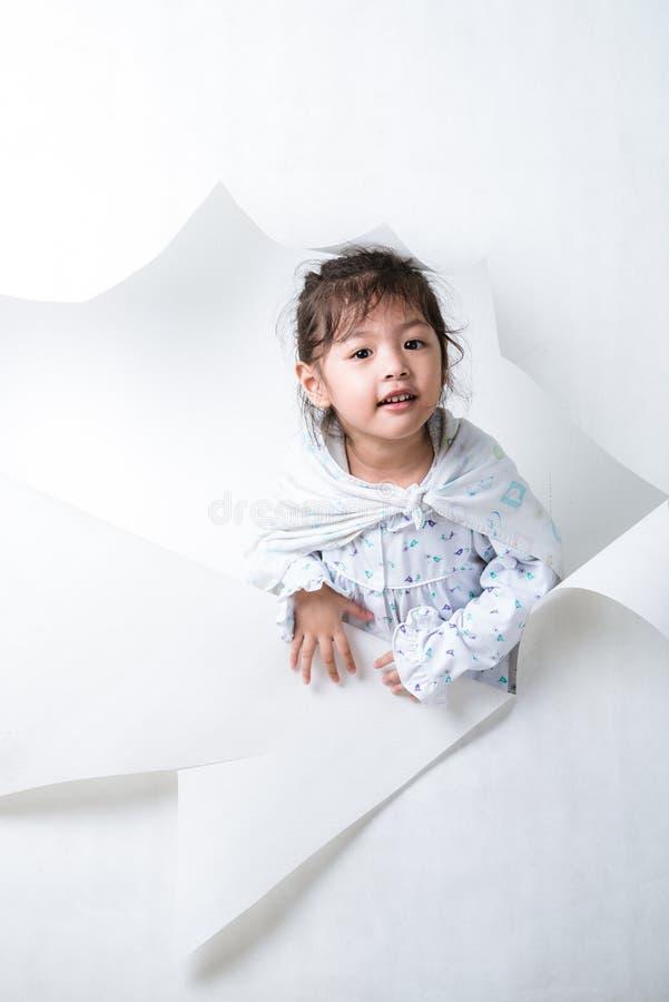 Muchacha que sale de un agujero en el fondo blanco #1 fotos de archivo libres de regalías