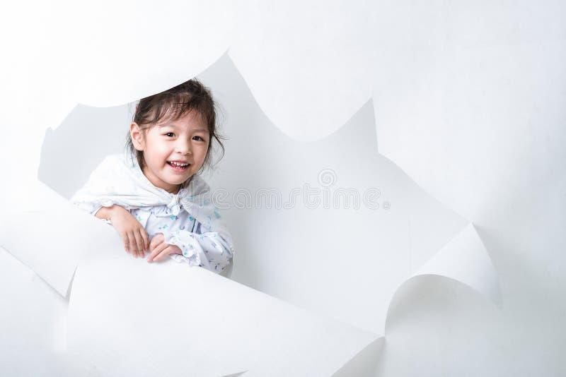 Muchacha que sale de un agujero en el fondo blanco #2 imágenes de archivo libres de regalías
