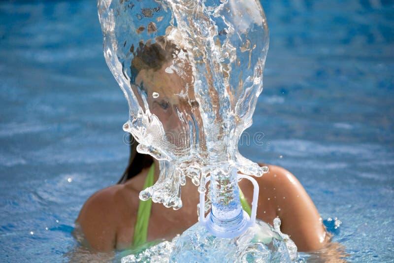Muchacha que salpica el agua en la piscina foto de archivo libre de regalías