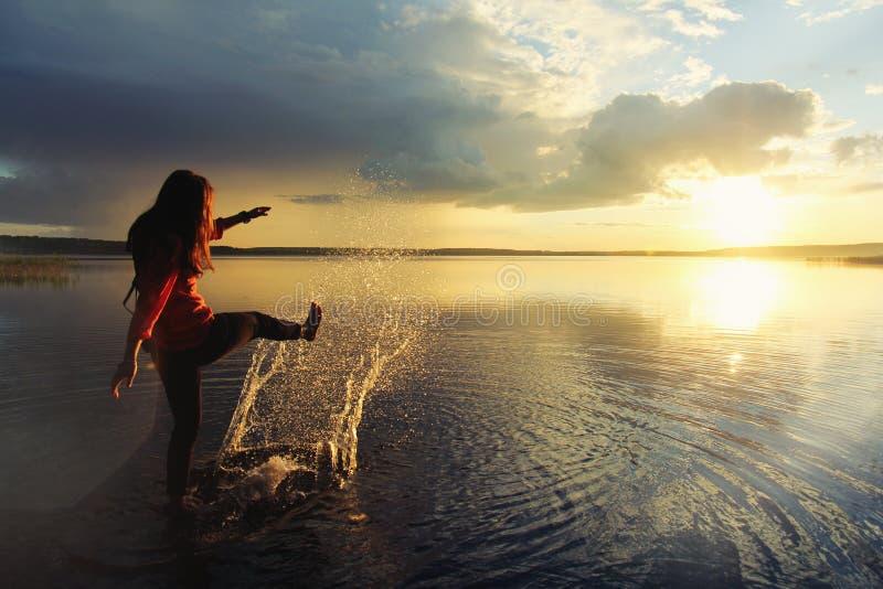 Muchacha que salpica en el agua en el lago y que mira la puesta del sol hermosa foto de archivo libre de regalías