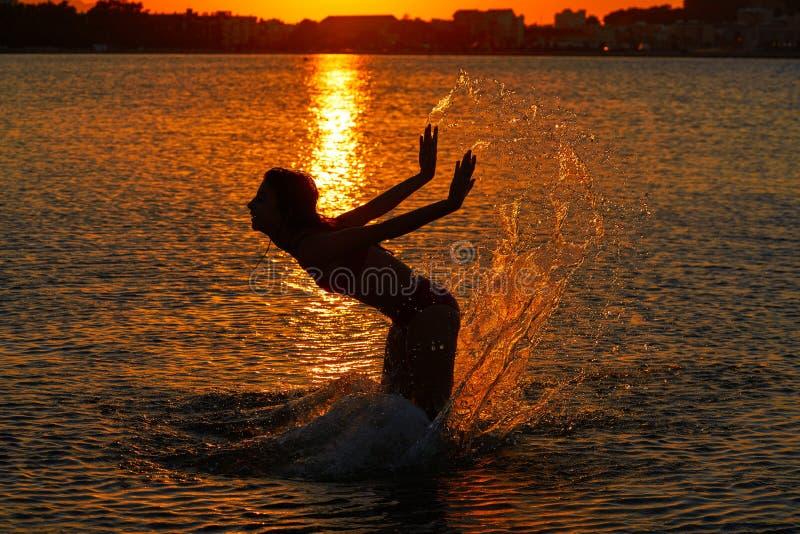 Muchacha que salpica las manos del agua en la playa de la puesta del sol fotos de archivo