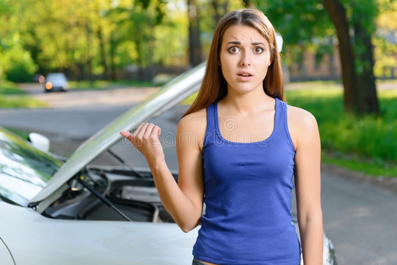 Muchacha que señala en el coche con el capo abierto foto de archivo libre de regalías