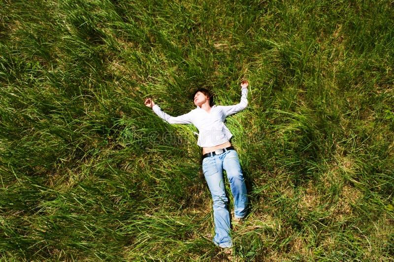 Muchacha que se acuesta de hierba fotos de archivo