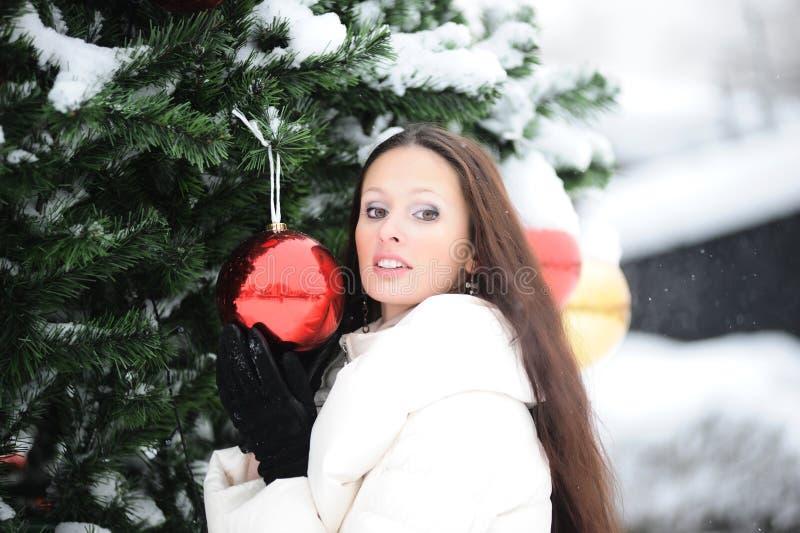 Muchacha que se coloca al lado del árbol de navidad foto de archivo libre de regalías