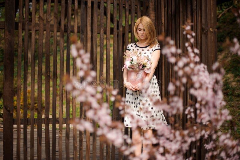 Muchacha que se coloca cerca de la cerca con una caja de flores imagenes de archivo