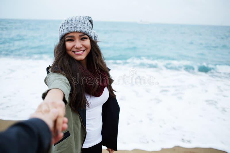 Muchacha que se coloca cerca del agua que ríe y que tira de su mano simple imagen de archivo