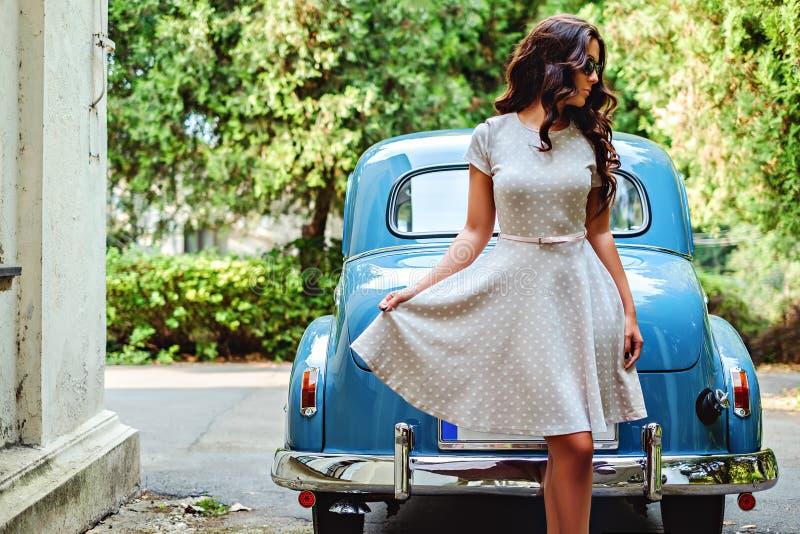 Muchacha que se coloca delante del coche azul clásico fotos de archivo