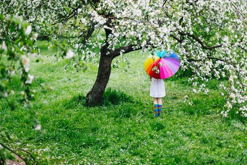 Muchacha que se coloca en el jardín floreciente con el arco iris-paraguas colorido Primavera, al aire libre imagen de archivo
