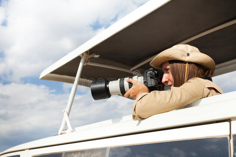 Muchacha que se coloca en jeep abierto del safari del tejado con la cámara imagenes de archivo
