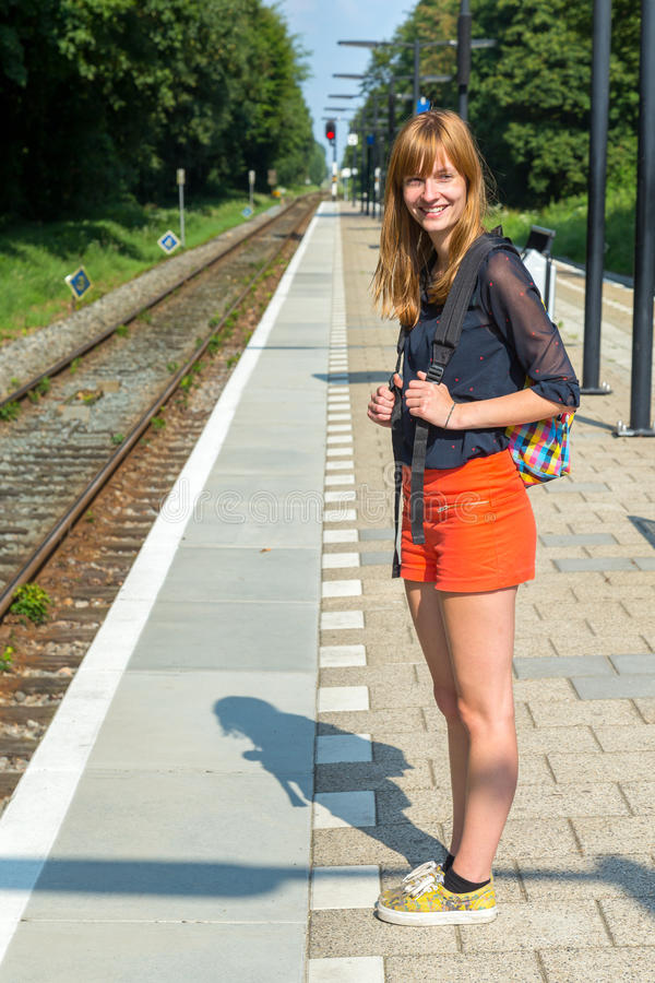Muchacha que se coloca en la estación que espera en el tren imágenes de archivo libres de regalías