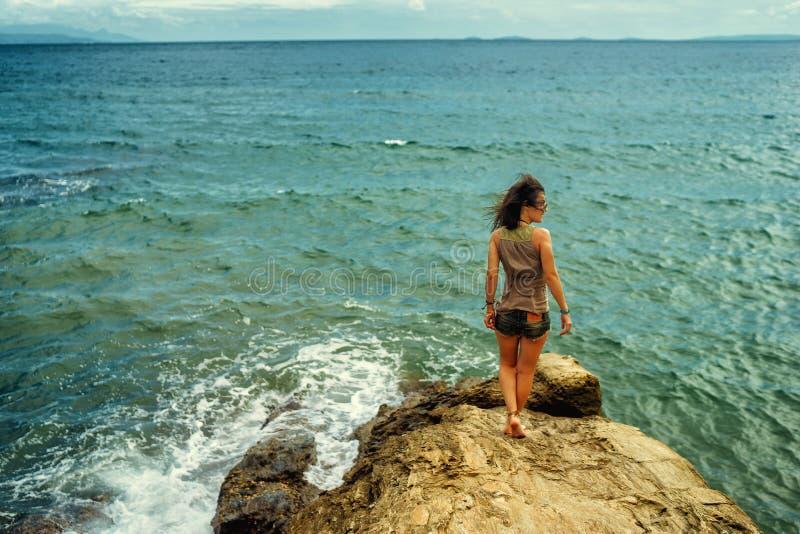 Muchacha que se coloca en rocas costeras del mar Forma de vida sana del bienestar imagen de archivo libre de regalías