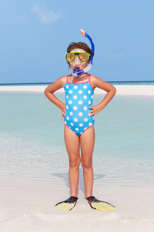 Muchacha que se coloca en tubo respirador y aletas que llevan de la playa imagen de archivo