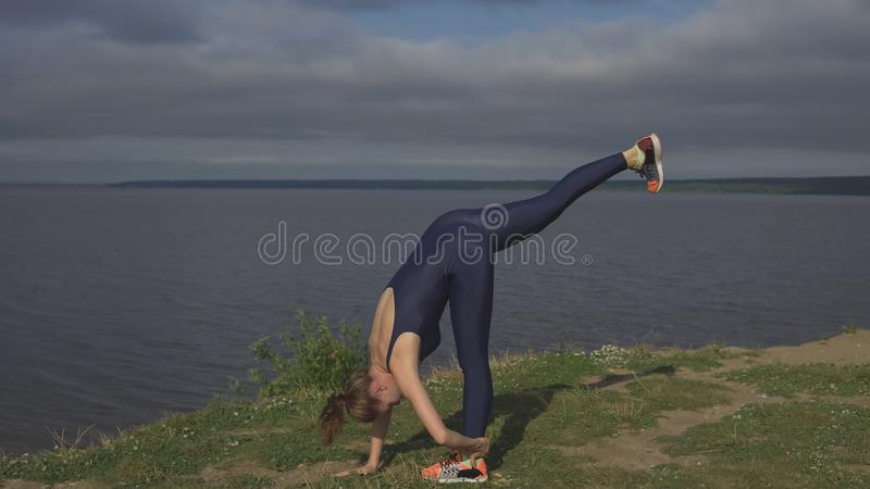 Muchacha que se coloca en una pierna, entrenamiento de la balanza, yoga foto de archivo