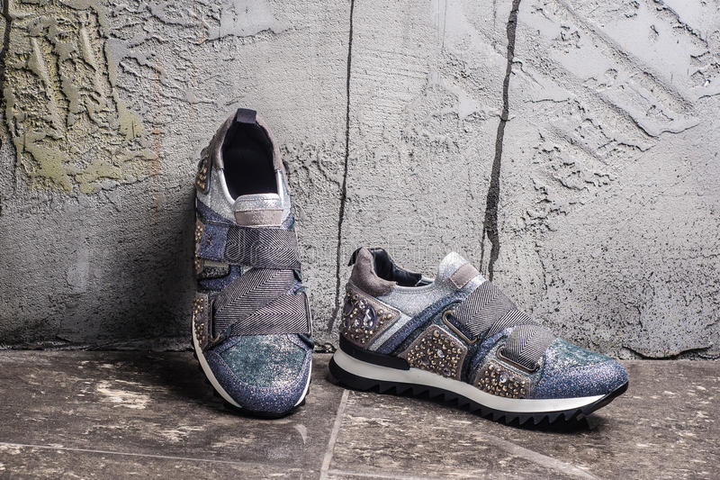 Muchacha que se coloca en zapatillas de deporte de moda estilo urbano de la moda imagen de archivo libre de regalías