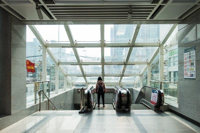 Muchacha que se coloca solamente de mirada hacia fuera de la ventana de la estación de metro urbana D imagen de archivo