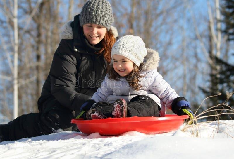 Muchacha que se divierte con su madre durante invierno fotografía de archivo libre de regalías
