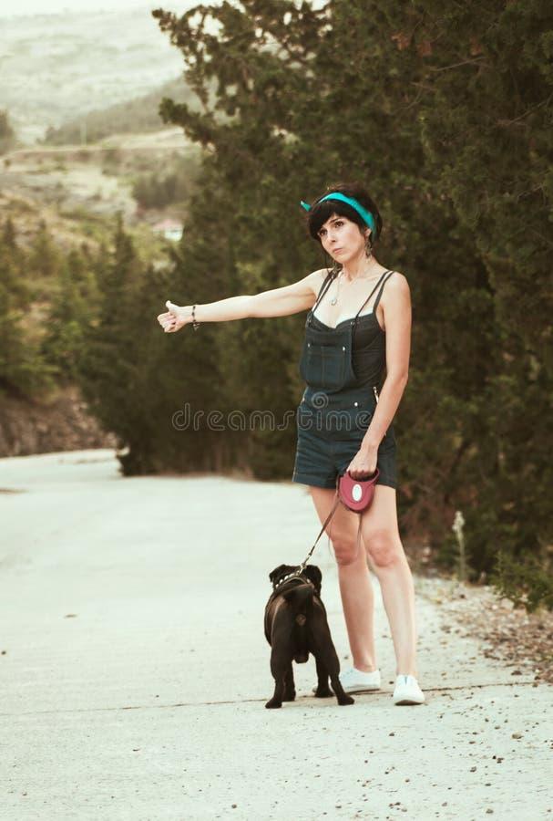 Muchacha que se divierte con su perro del barro amasado fotografía de archivo
