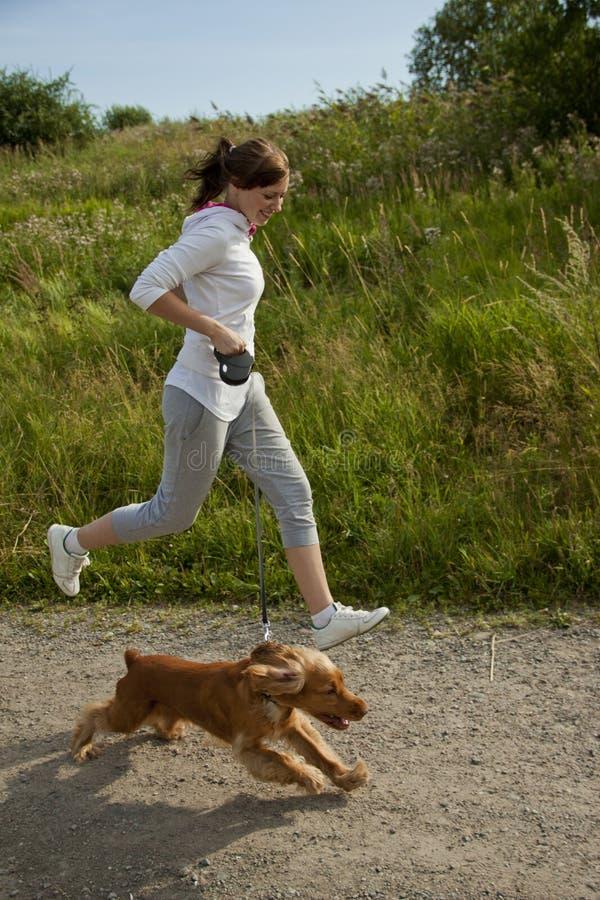 Muchacha que se ejecuta con su perro fotos de archivo libres de regalías
