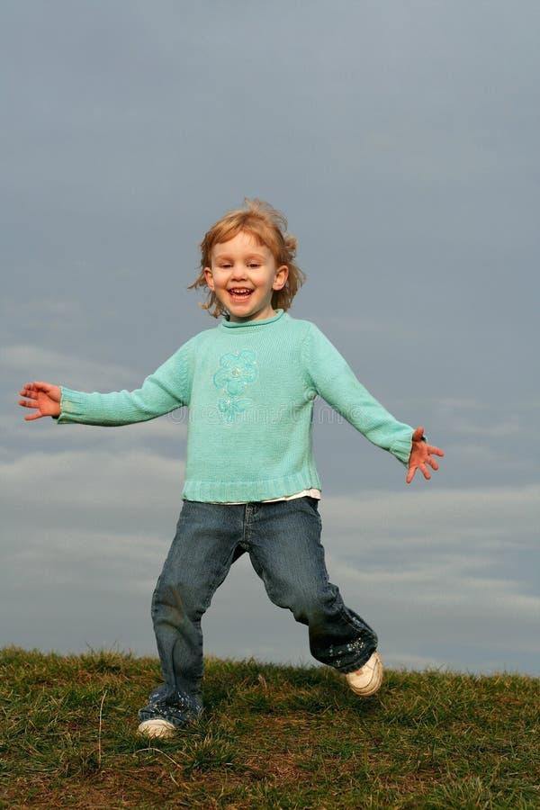 Muchacha que se ejecuta en la colina de la hierba foto de archivo