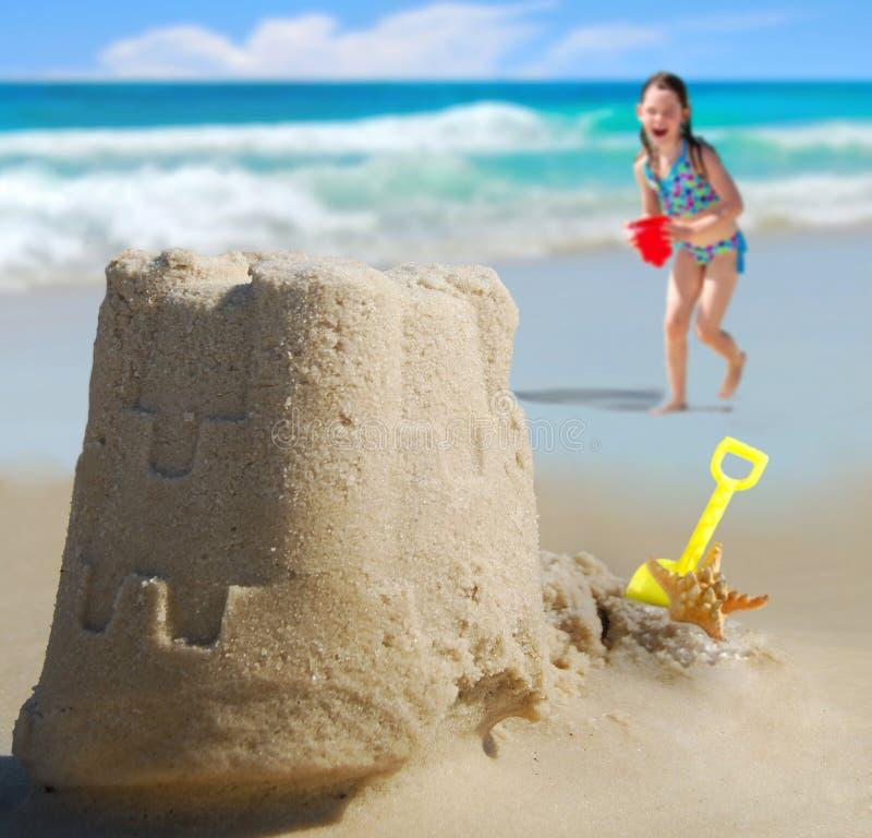 Muchacha que se ejecuta hacia castillo de la arena en la costa imagen de archivo