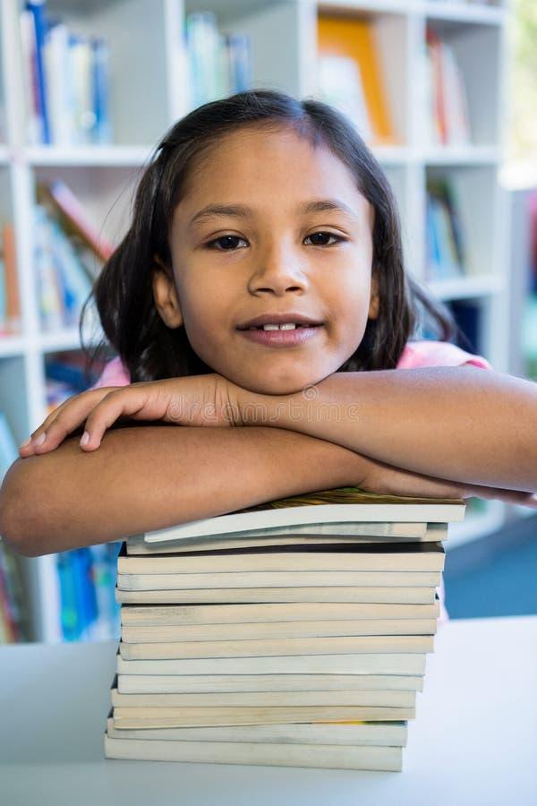 Muchacha que se inclina en los libros en la tabla en biblioteca escolar fotografía de archivo