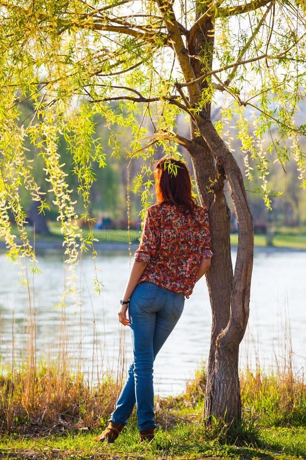Muchacha que se inclina en un árbol, pensativo imagen de archivo libre de regalías