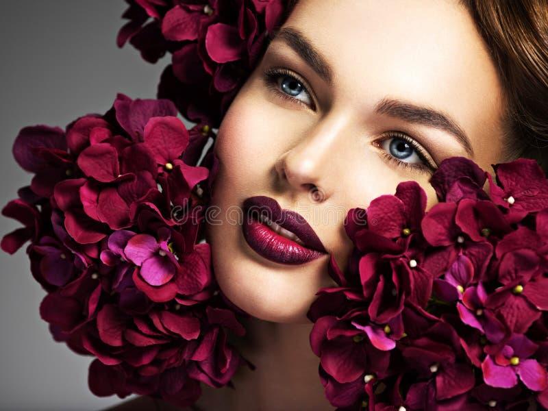 Muchacha que se pregunta en flores con maquillaje fotos de archivo