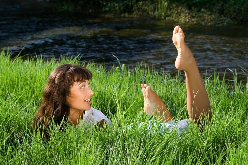 Muchacha que se pregunta liying en hierba verde fresca foto de archivo