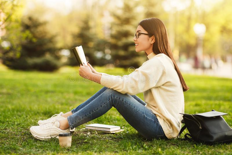 Muchacha que se prepara para las conferencias, libro de lectura en campus de la universidad fotografía de archivo libre de regalías