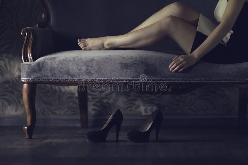 Muchacha que se reclina sobre el sofá imagen de archivo libre de regalías