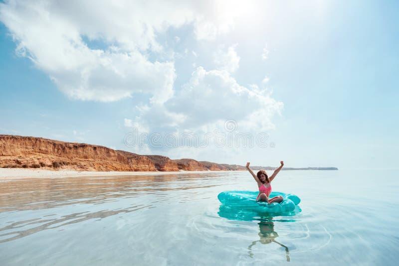 Muchacha que se relaja en el anillo inflable en la playa imagenes de archivo