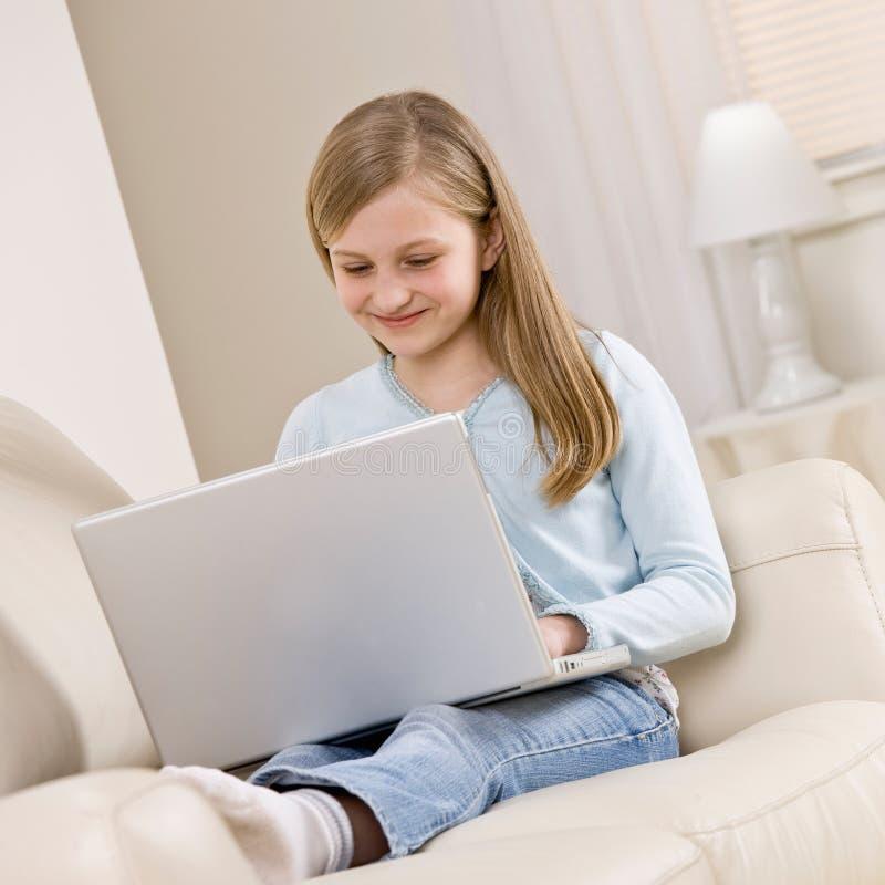 Muchacha que se relaja en el sofá en sala de estar fotos de archivo