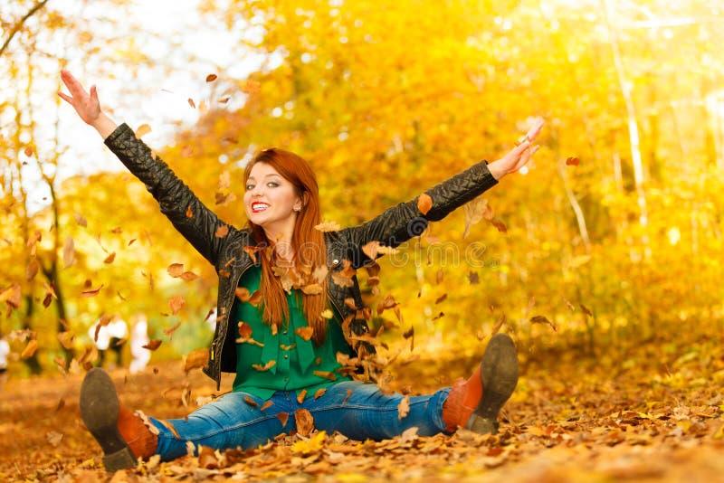 Muchacha que se relaja en hojas que lanzan del parque del otoño para arriba en el aire fotografía de archivo libre de regalías