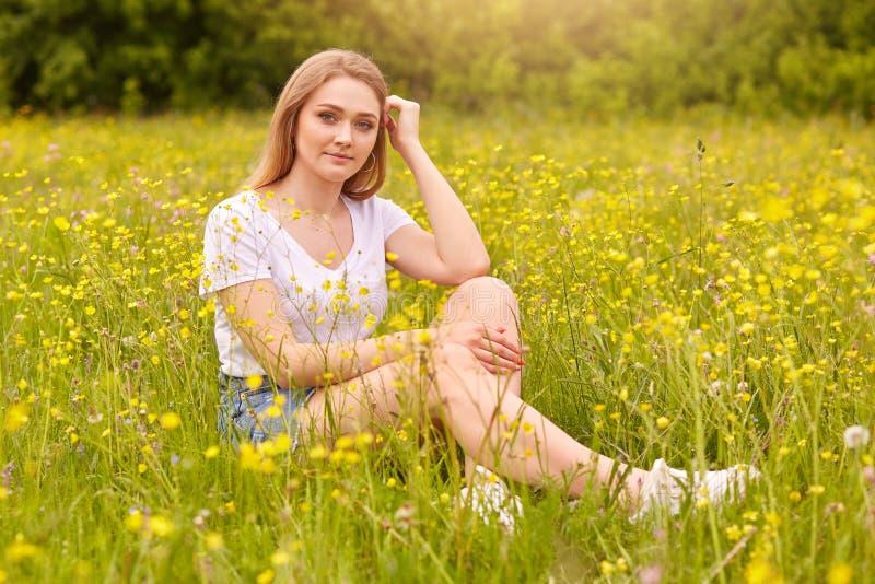 Muchacha que se relaja en prado, mujer joven hermosa rubia que se sienta en la hierba rodeada con las flores del campo y que disf fotografía de archivo libre de regalías